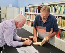 Ken Heffernan and Neil Gillespie examine rare books in the Gillespie Collection.