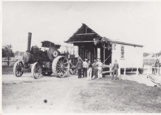 Part of the former Ginninderra Farmers Union hall crossing Halls Creek on its way to the Hall showground, 1930, where it was used as a show pavilion. It is on a jinker  towed by Tom Gribble's traction engine. Find out more about the Gribble family and the Farmers Union at 'Rediscovering Ginninderra'